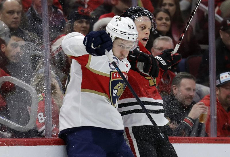 Florida Panthers right wing Evgenii Dadonov, left, is checked by Chicago Blackhawks defenseman Connor Murphy during the second period of an NHL hockey game Sunday, Dec. (AP Photo/Nam Y. Huh)