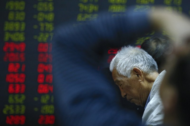 In this Oct. 24, 2018, photo, an investor reacts as he and investors monitor stock prices at a brokerage house in Beijing. (AP Photo/Andy Wong)