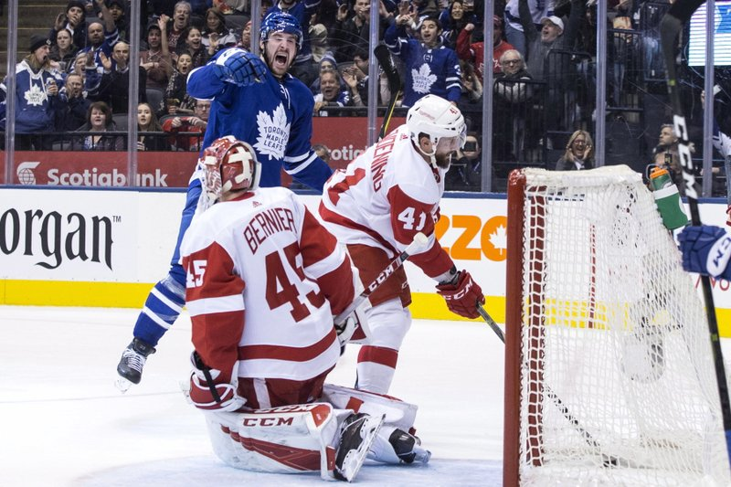 Detroit Red Wings' Luke Glendening (41) retrieves the puck from the net as Toronto Maple Leafs' Frederik Gauthier celebrates after scoring his team's second goal against Red Wings goaltender Jonathan Bernier during second-period NHL hockey game action in Toronto, Sunday, Dec. (Chris Young/The Canadian Press via AP)