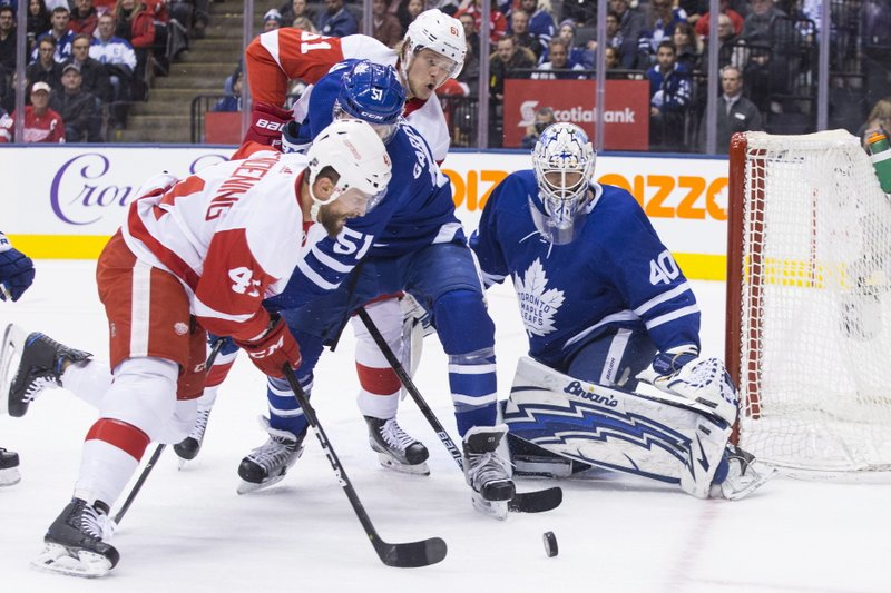 Detroit Red Wings Luke Glendening, left, goes after a loose puck in front of Toronto Maple Leafs goaltender Garret Sparks during first period NHL hockey action in Toronto, on Sunday, Dec. (Chris Young/The Canadian Press via AP)