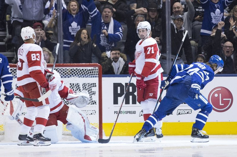 Toronto Maple Leafs right wing Kasperi Kapanen, right, turns after scoring his team's opening goal as Detroit Red Dylan Larkin (71) looks on during first period NHL hockey action in Toronto, Sunday, Dec. (Chris Young/The Canadian Press via AP)