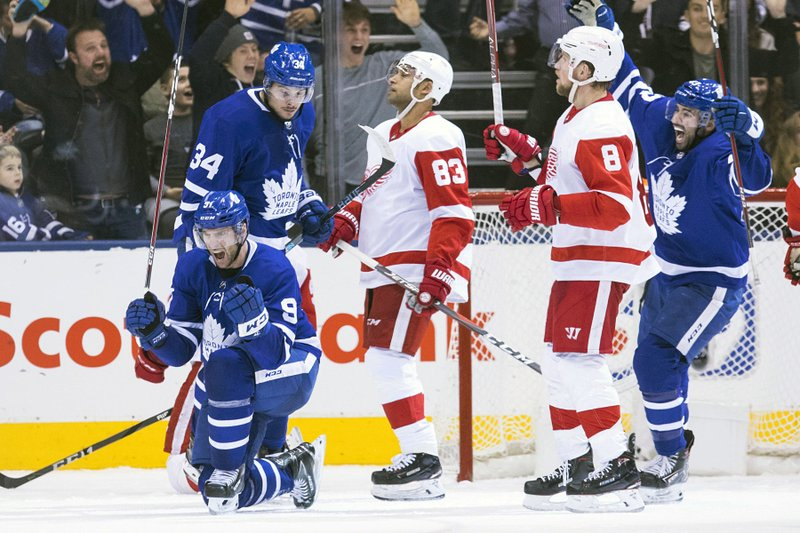 Toronto Maple Leafs' John Tavares, left, celebrates after scoring his team's game-tying goal against the Detroit Red Wings in the final seconds of third period NHL hockey action in Toronto, on Sunday, Dec. (left) and Nazem Kadri (right) and Detroit's Trevor Daley (83) and Justin Abdelkader (8) look on. (Chris Young/The Canadian Press via AP)