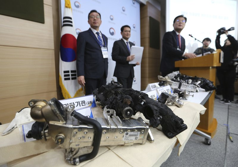 South Korean Transport Ministry officials hold a press conference as damaged gears of a BMW which engine had caught fire are displayed at the government complex in Seoul, South Korea, Monday, Dec. ($9.9 million) and file a criminal complaint against the company with state prosecutors over an allegedly botched response to dozens of engine fires reported in the country. (AP Photo/Ahn Young-joon)