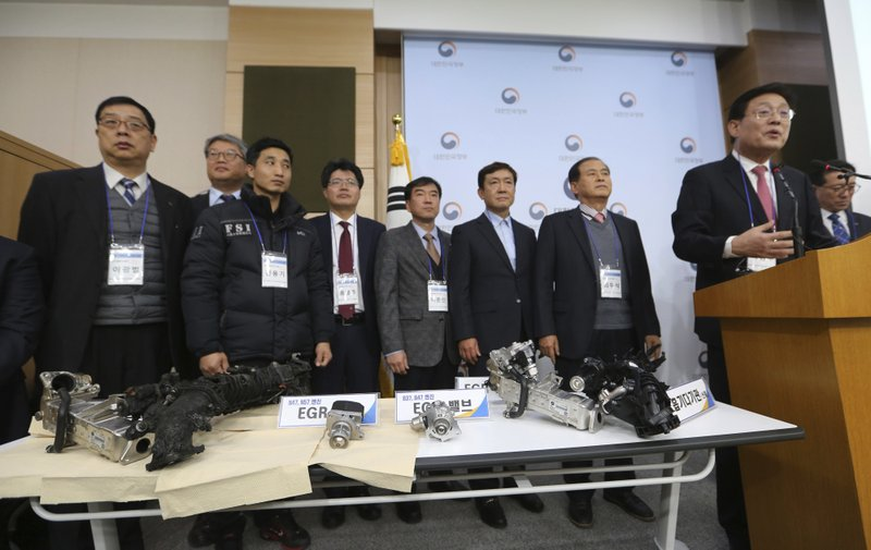 South Korean Transport Ministry officials and members of investigative panel on BMW engine hold a press conference as damaged gears of a BMW which engine had caught fire are displayed at the government complex in Seoul, Monday, Dec. ($9.9 million) and file a criminal complaint against the company with state prosecutors over an allegedly botched response to dozens of engine fires reported in the country. (AP Photo/Ahn Young-joon)