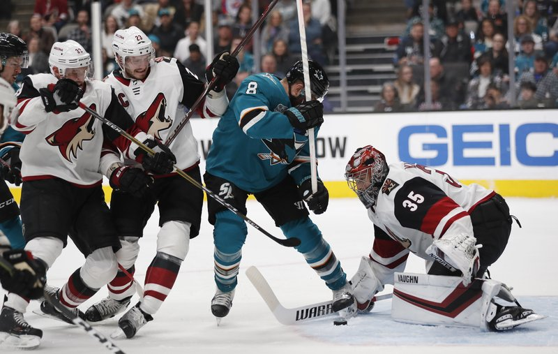 San Jose Sharks' Joe Pavelski (8) battles for the puck against Arizona Coyotes' Darcy Kuemper (35), Alex Goligoski (33) and Oliver Ekman-Larsson (23) in the second period of an NHL hockey game in San Jose, Calif. (AP Photo/Josie Lepe)
