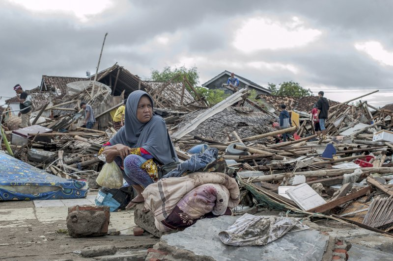 In this Monday, Dec. 24, 2018, photo, a tsunami survivor sits on a pice of debris as she salvages items from the location of her house in Sumur, Indonesia. (AP Photo/Fauzy Chaniago)