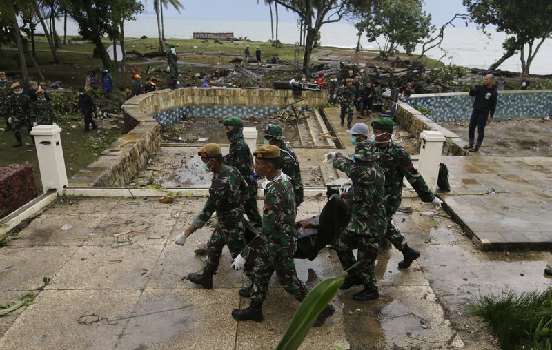 In this Monday, Dec. 24, 2018, photo, Indonesian soldiers carry the bodies of tsunami victims at a beach resort in Tanjung Lesung Indonesia. (AP Photo/Achmad Ibrahim)