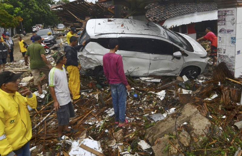 In this Sunday, Dec. 23, 2018, photo, people inspect the wreckage of a car swept away by a tsunami in Carita, Indonesia. (AP Photo)