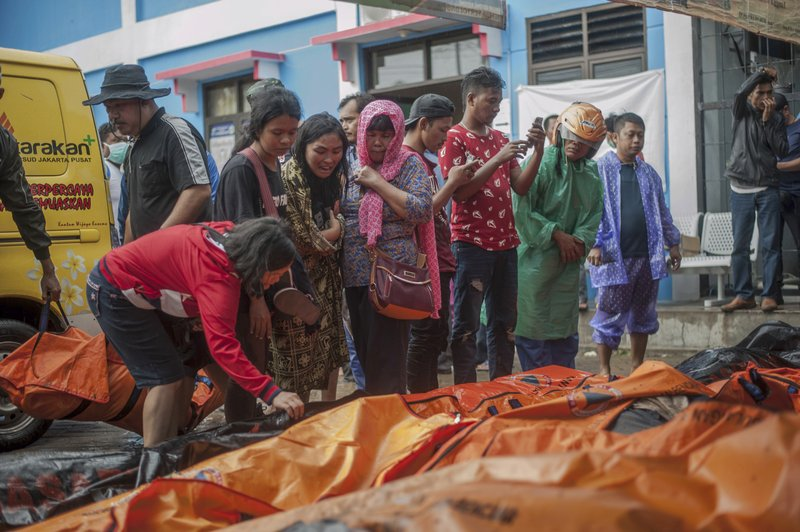 In this Sunday, Dec. 23, 2018, photo, People search for relatives among the bodies of tsunami victims in Carita, Indonesia. (AP Photo/Fauzy Chaniago)