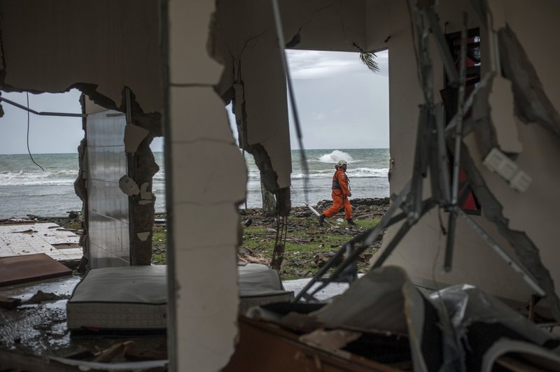 In this Sunday, Dec. 23, 2018, photo, a rescuer is seen through a damaged house as he takes part in a search operation of tsunami victims in Carita, Indonesia. (AP Photo/Fauzy Chaniago)