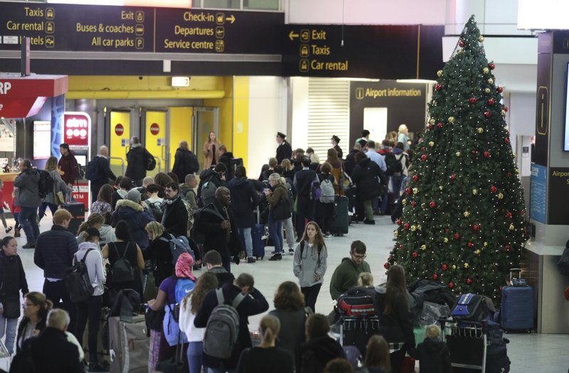Passengers at Gatwick airport wait for their flights following the delays and cancellations brought on by drone sightings near the airfield, in London, Friday Dec. (John Stillwell/PA via AP)