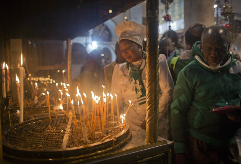Christian worshippers light candles at the Church of the Nativity, traditionally recognized by Christians to be the birthplace of Jesus Christ, in the West Bank city of Bethlehem, Sunday, Dec. (AP Photo/Nasser Nasser)