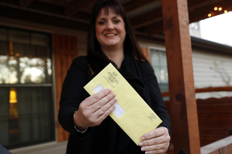 In this Dec. 20, 2018 photo, Reagen Adair holds on to an RIP Medical Debt yellow envelope as she poses for a photo at her home in Murchison, Texas. (AP Photo/Tony Gutierrez)