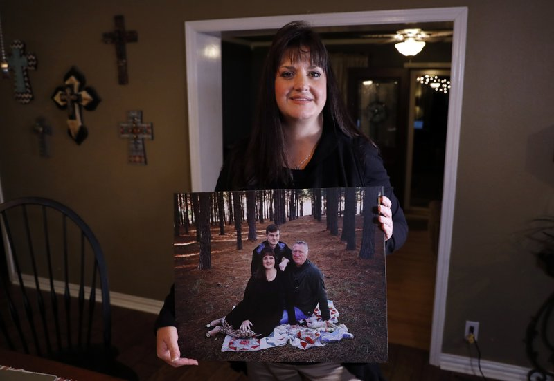 In this Thursday, Dec. 20, 2018 photo, Reagen Adair poses for a photo at her home holding a portrait of herself, with her husband Dale and son Mason, in Murchison, Texas. (AP Photo/Tony Gutierrez)