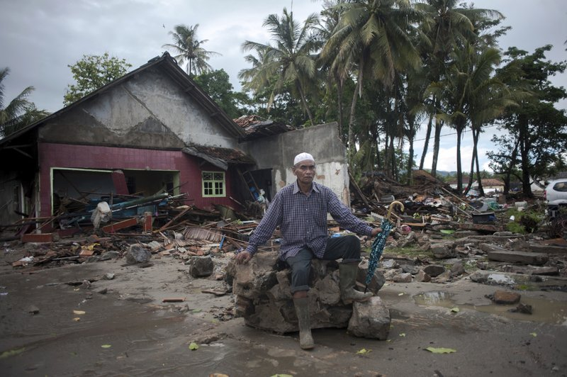 A man sits on a piece of debris at a tsunami-ravaged village in Sumur, Indonesia, Monday, Dec. 24, 2018. (AP Photo/Fauzy Chaniago)