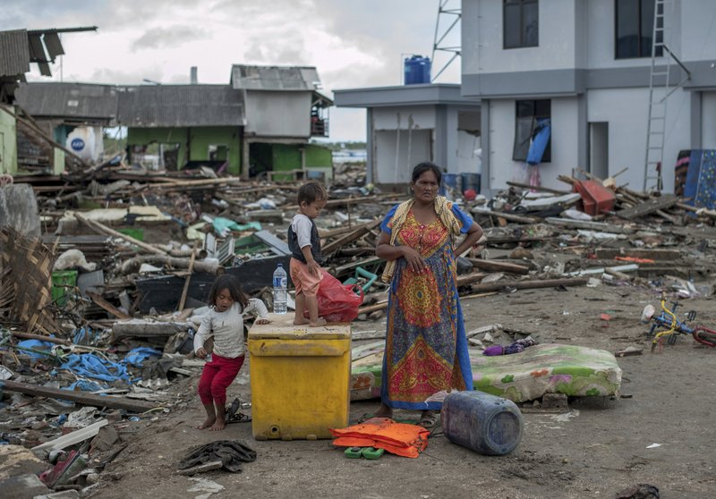 A woman and her children inspect the damage at a tsunami-ravaged village in Sumur, Indonesia, Monday, Dec. (AP Photo/Fauzy Chaniago)