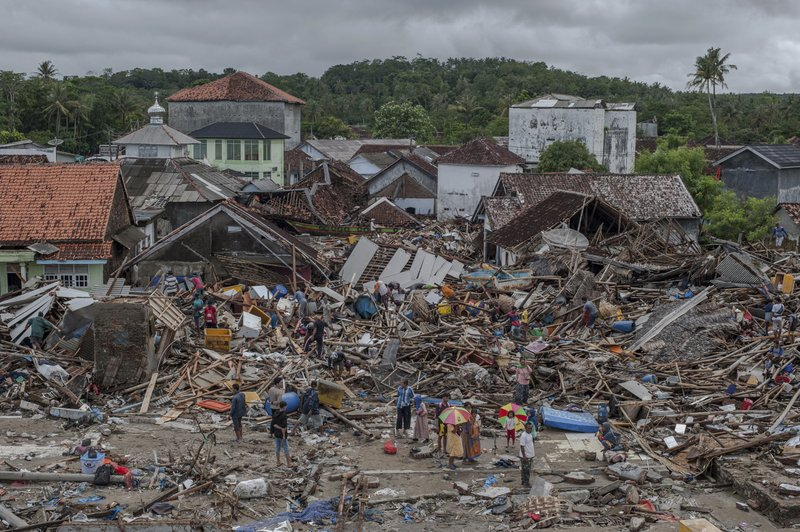 People inspect the damage at a tsunami-ravaged village in Sumur, Indonesia, Monday, Dec. 24, 2018. Doctors are working to help survivors and rescuers are looking for more victims from a deadly tsunami that smashed into beachside buildings along an Indonesian strait. (AP Photo/Fauzy Chaniago)