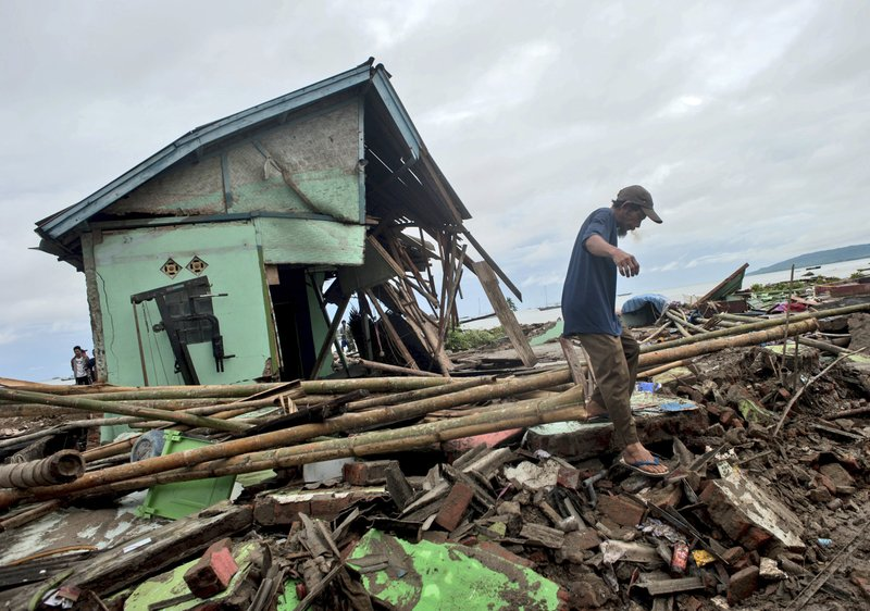 A man makes his way past a house badly damaged by a tsunami in Sumur, Indonesia, Monday, Dec. 24, 2018. (AP Photo/Fauzy Chaniago)