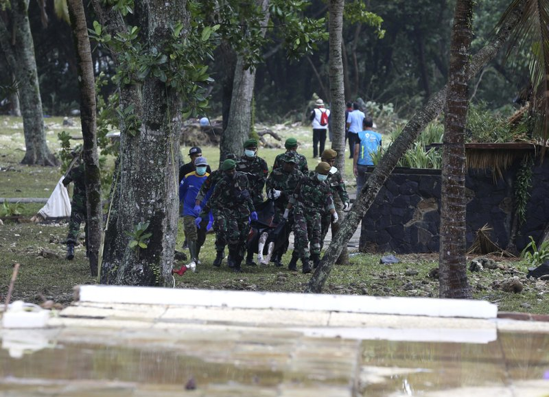 Indonesian soldiers carry the bodies of tsunami victims at Tanjung Lesung beach, Indonesia, Monday, Dec. (AP Photo/Achmad Ibrahim)