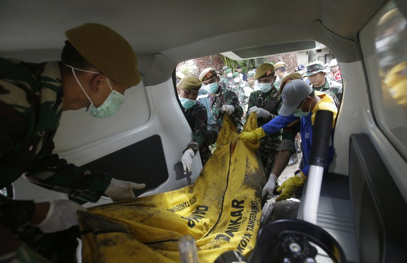 Indonesian soldiers load the body of a tsunami victim into an ambulance at Tanjung Lesung beach resort, Indonesia, Monday, Dec. (AP Photo/Achmad Ibrahim)
