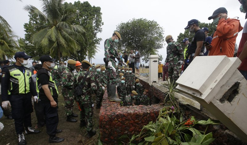 Indonesian soldiers and rescuers search the tsunami victims at a beach resort in Tanjung Lesung, Indonesia, Monday, Dec. (AP Photo/Achmad Ibrahim)