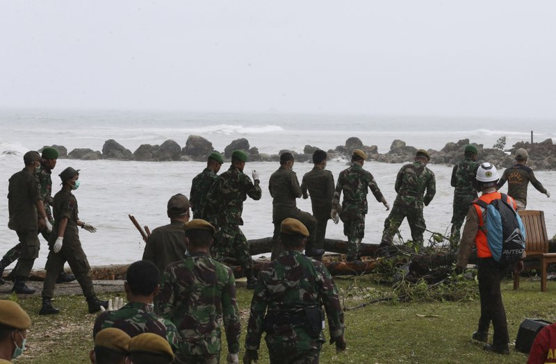 Indonesian soldiers and rescue team search the tsunami victims at a beach resort in Tanjung Lesung, Indonesia, Monday, Dec. (AP Photo/Achmad Ibrahim)