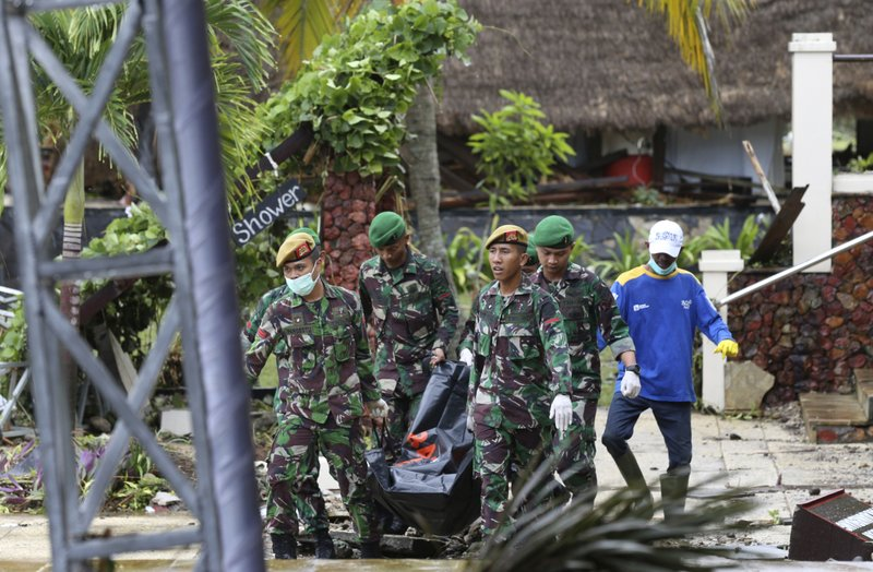 Indonesian soldiers and rescuers carry the bodies of tsunami victims at Tanjung Lesung beach resort, Indonesia, Monday, Dec. (AP Photo/Achmad Ibrahim)