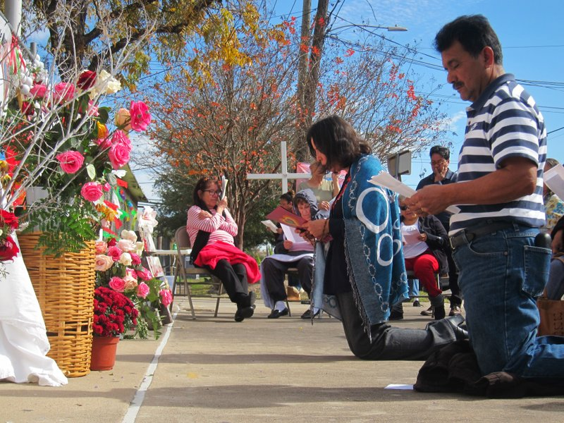 In this Dec. 16, 2018 photo, Rosario Rodriguez and Jose Guevara lead members of St. Stephen Catholic Church as they pray the rosary in front of a chain link fence surrounding their closed church in Houston, Texas. (AP Photo/Juan Lozano)