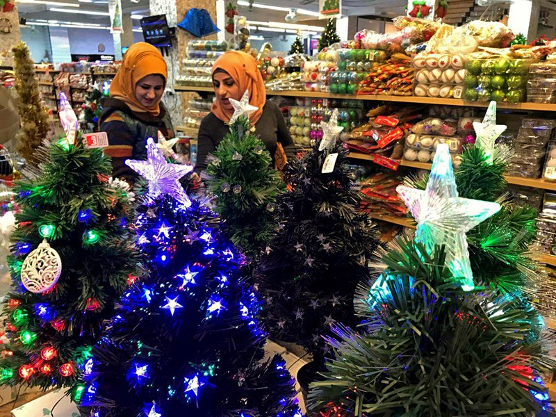 Iraqis shop for Christmas decorations in Baghdad, Iraq, Monday, Dec. 24, 2018. Although the number of Christians has dropped in Iraq, Christmas a national holiday, is very popular in the capital. (AP Photo/Ali Abdul Hassan)