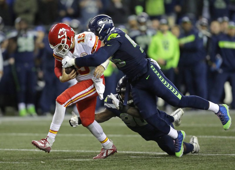 Kansas City Chiefs quarterback Patrick Mahomes (15) is tackled by Seattle Seahawks defensive end Frank Clark, right, during the second half of an NFL football game, Sunday, Dec. (AP Photo/Stephen Brashear)