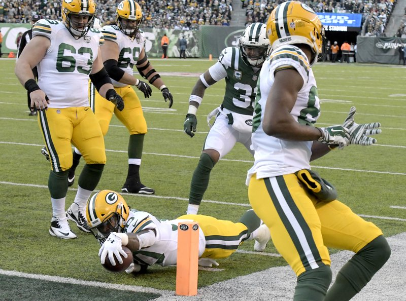 Green Bay Packers running back Jamaal Williams, bottom, dives in for a touchdown as New York Jets strong safety Jamal Adams, center, looks on during the first half of an NFL football game, Sunday, Dec. (AP Photo/Bill Kostroun)