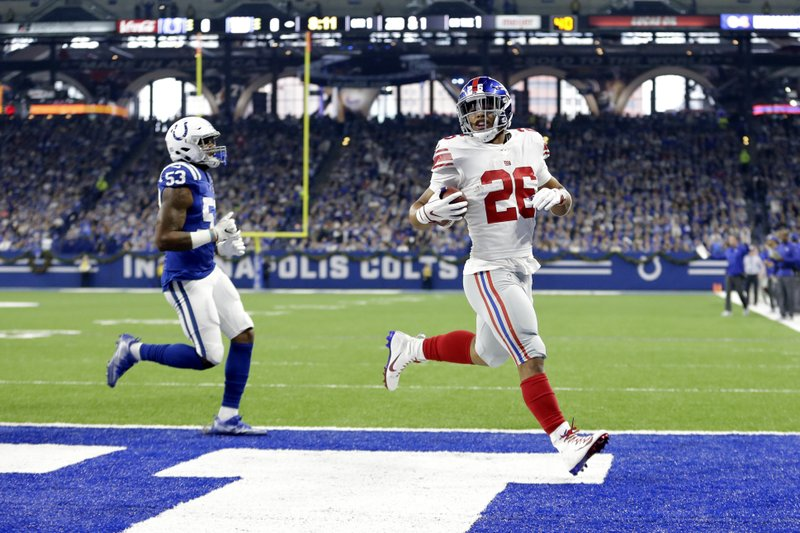 New York Giants running back Saquon Barkley (26) runs in for a touchdown in front of Indianapolis Colts outside linebacker Darius Leonard (53) during the first half of an NFL football game in Indianapolis, Sunday, Dec. (AP Photo/AJ Mast)