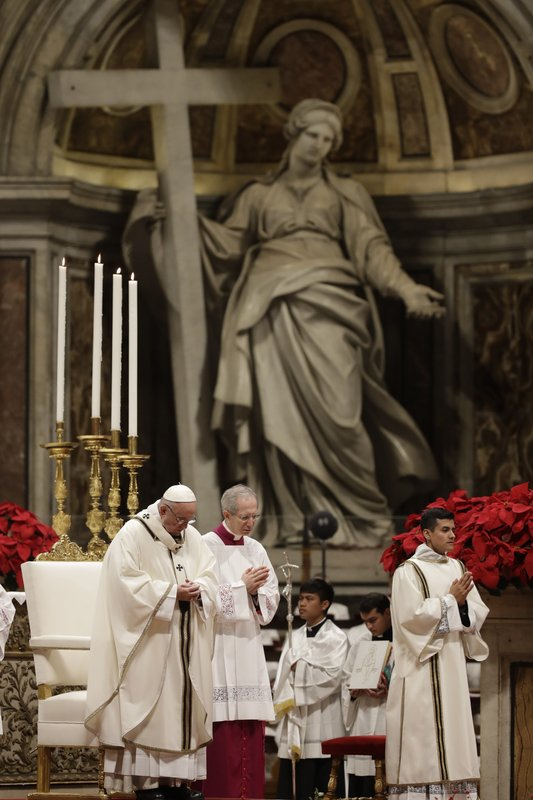 Pope Francis, left, celebrates the Christmas Eve Mass in St. Peter's Basilica at the Vatican, Monday, Dec. (AP Photo/Alessandra Tarantino)