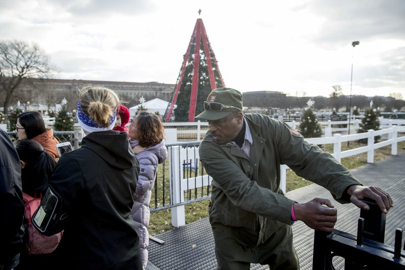 A National Park Service employee closes the gate to visitors at the National Christmas Tree on the Ellipse near the White House, Monday, Dec. (AP Photo/Andrew Harnik)