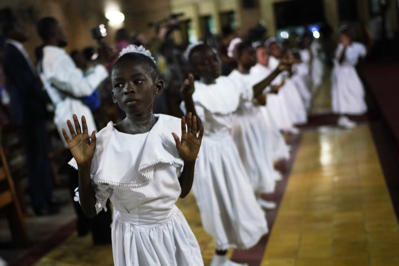 Congolese children dance before Msg. Fridolin Ambongo, the the newly appointed Archibishop of Kinshasa, delivers the homily during an early midnight mass at the Notre Dame du Congo Cathedral in Kinshasa, Congo, Monday Dec. (AP Photo/Jerome Delay)
