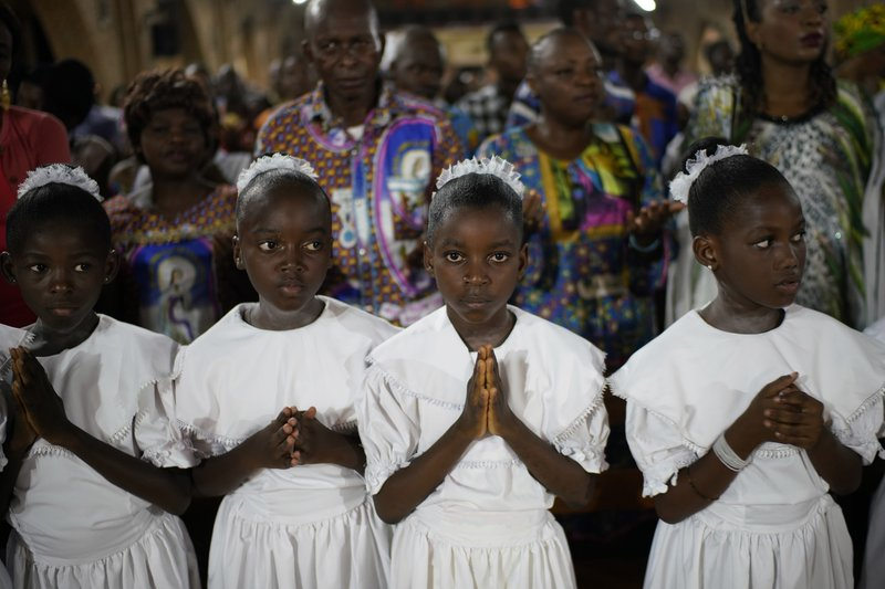 Congolese children pray as Msg. Fridolin Ambongo, the the newly appointed Archibishop of Kinshasa, delivers the homily during an early midnight mass at the Notre Dame du Congo Cathedral in Kinshasa, Congo, Monday Dec. (AP Photo/Jerome Delay)