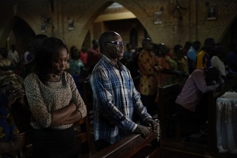 Congolese worshipers listen to Msg. Fridolin Ambongo, the the newly appointed Archibishop of Kinshasa, deliver the homily during an early midnight mass at the Notre Dame du Congo Cathedral in Kinshasa, Congo, Monday Dec. (AP Photo/Jerome Delay)