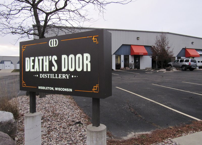 In this Nov. 26, 2018 photo, a sign sits outside Death's Door Spirits in Middleton, Wis. A competing distillery has submitted a winning bid of nearly $2. (Barry Adams/Wisconsin State Journal via AP)
