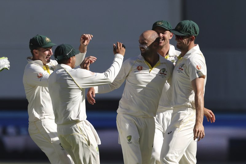 Australian players reach for bowler Australia's Nathan Lyon, third right, after he dismissed India's Murali Vijay during play in the second cricket test between Australia and India in Perth, Australia, Monday, Dec. (AP Photo/Trevor Collens)