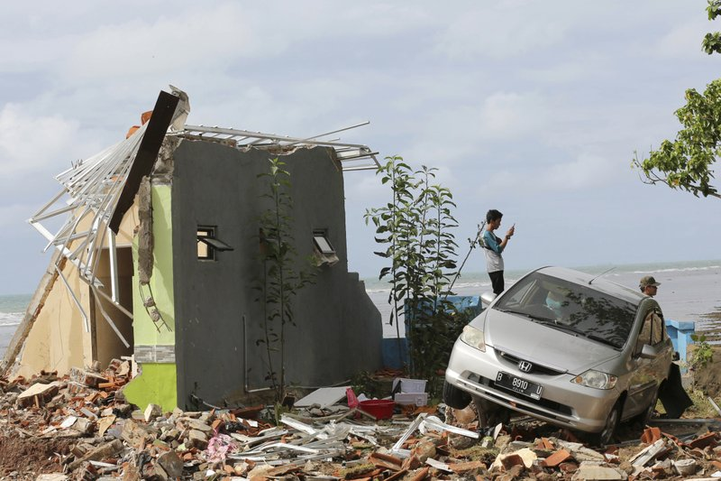 A man takes a photo with his mobile phone at a cottage damaged by a tsunami in Carita beach, Indonesia, Monday, Dec. (AP Photo/Tatan Syuflana)