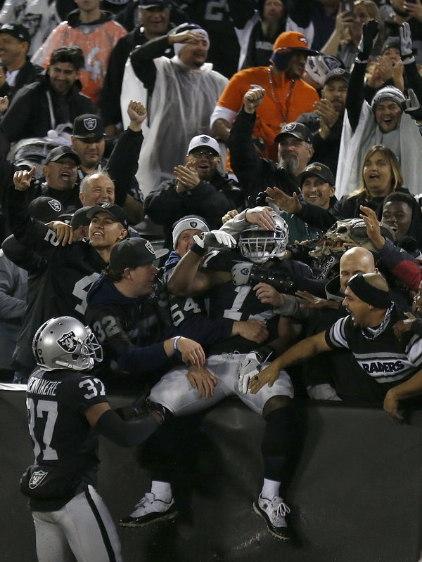 Oakland Raiders' Dwayne Harris, center, celebrates with fans after returning a punt for a touchdown against the Denver Broncos during the first half of an NFL football game in Oakland, Calif. (AP Photo/D. Ross Cameron)