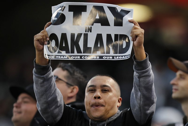 An Oakland Raiders fan holds up a sign before an NFL football game between the Raiders and the Denver Broncos in Oakland, Calif. (AP Photo/John Hefti)