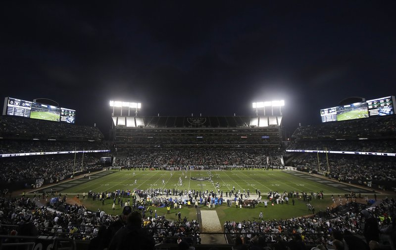Fans watch the opening kickoff from a general view of Oakland Alameda County Coliseum during the first half of an NFL football game between the Oakland Raiders and the Denver Broncos in Oakland, Calif. (AP Photo/Jeff Chiu)