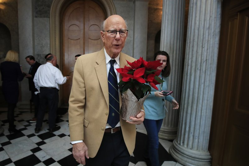 Sen. Pat Roberts, R-Kan., carries a poinsettia on Capitol Hill in Washington, Monday, Dec. 24, 2018, after a pro forma session, a brief meeting of the Senate, during a partial government shutdown. (AP Photo/Manuel Balce Ceneta)