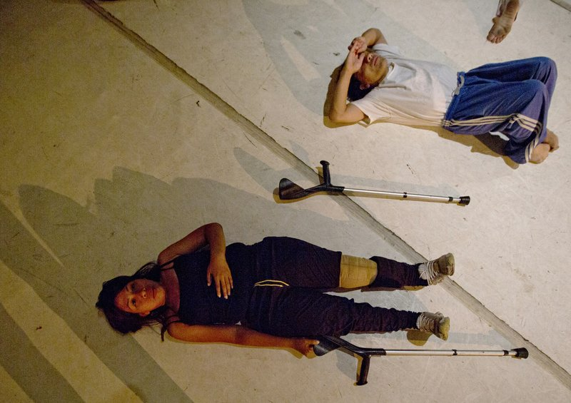 In this Dec. 4, 2018 photo, dancers stretch prior to their performance in the contemporary dance production Ubuntu, at the Teresa Carreno Theater in Caracas, Venezuela. (AP Photo/Fernando Llano)
