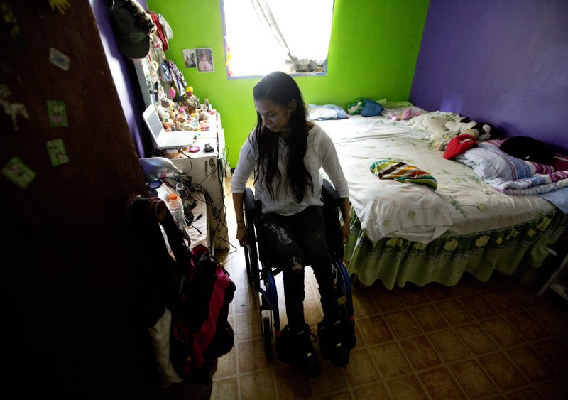 This Dec. 17, 2018 photo shows dancer Iraly Yanez in her home in Caracas, Venezuela. The ballerina was hit by a stray bullet on New Year's eve in 2010 as she entered her home in a crime-ridden slum. (AP Photo/Fernando Llano)