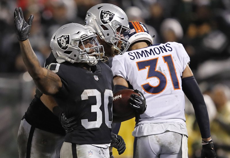 Oakland Raiders running back Jalen Richard (30) celebrates with Lee Smith after scoring a touchdown in front of Denver Broncos free safety Justin Simmons (31) during the second half of an NFL football game in Oakland, Calif. (AP Photo/John Hefti)