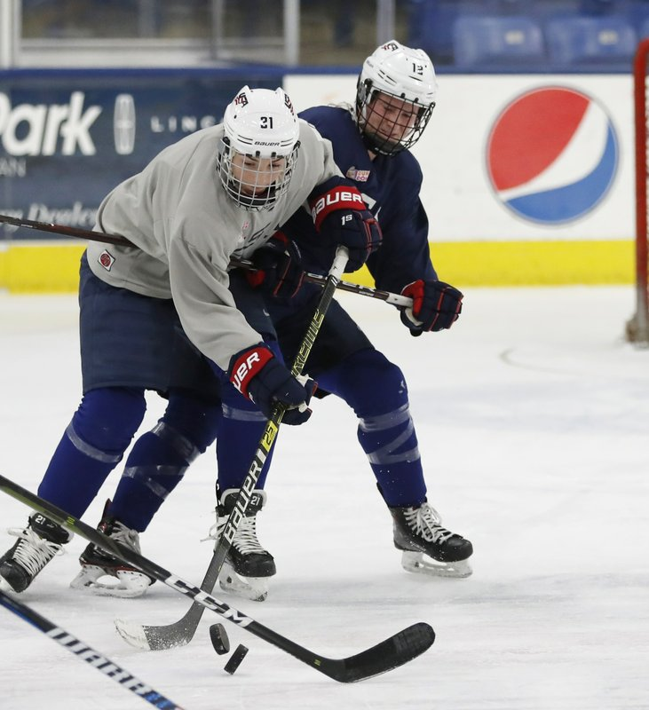 In a photo from, Thursday, Dec. 20, 2018, in Plymouth, Mich., USA Hockey forwards Hilary Knight, left, and Kelly Panneck chase the pucks during practice. (AP Photo/Carlos Osorio)