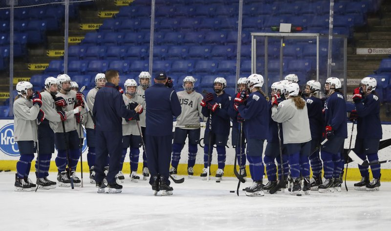 In a photo from, Thursday, Dec. 20, 2018, in Plymouth, Mich., members of the USA Hockey women's team listen to their coach during practice. (AP Photo/Carlos Osorio)