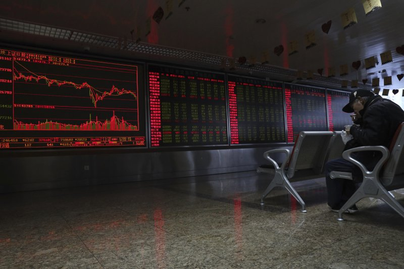 A Chinese man eats his meal at a brokerage in Beijing, China, Tuesday, Dec. 25, 2018. Japanese stocks plunged Tuesday and other Asian markets declined following heavy Wall Street losses triggered by President Donald Trump's attack on the U. (AP Photo/Ng Han Guan)
